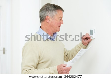 Worried Senior Man With Bill Turning Down Heating Thermostat
