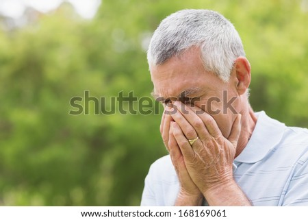 Worried senior man with head in hands at the park
