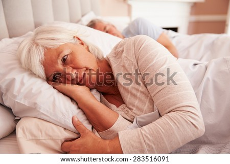 Worried Senior Woman Lying Awake In Bed