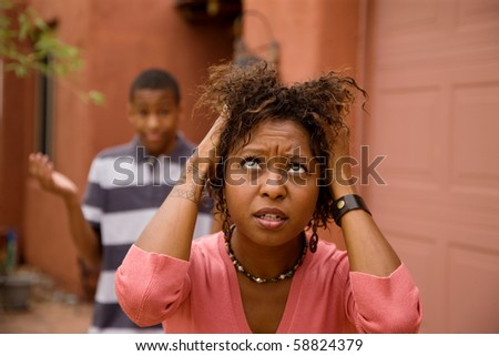 Worried single-mother with son pulling her hair - stock photo