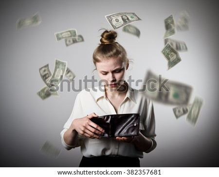 Worried slim woman is looking in a wallet. Dollars are falling. - stock photo