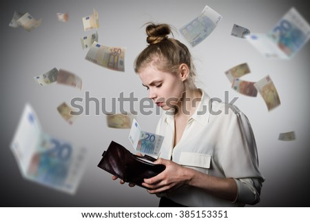 Worried slim woman is looking in a wallet. Euro are falling.