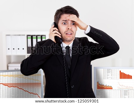 Worried stock broker talking on the phone backed by graphs depicting a crisis and a bear market with huge losses in the market - stock photo