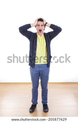 Worried stressed man screaming holding hands on his head, Casual troubled young man with frustration yelling - stock photo
