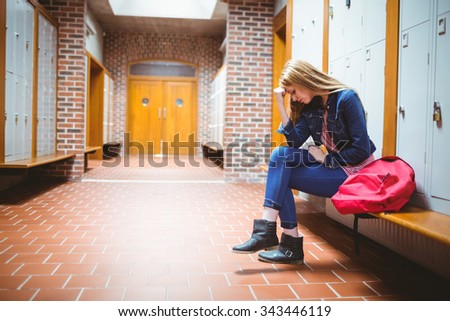 Worried student sitting with hand on head at the university - stock photo