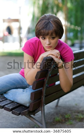 worried teen girl on the bench - stock photo