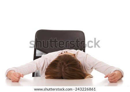 Worried teenage woman sleeping at the desk - stock photo