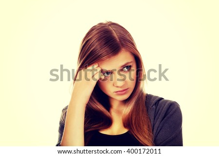 Worried teenage woman with folded arms - stock photo