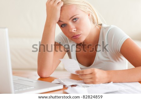 Worried woman accounting looking into the camera in the living room - stock photo