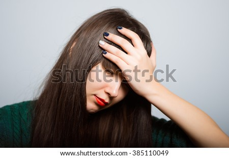 Worried woman have big problem. long-haired girl has a headache, a student in isolation on a gray background - stock photo