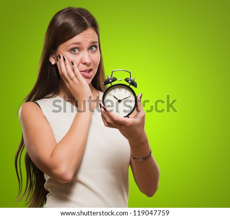 Worried Woman Holding Alarm Clock against a green background - stock photo