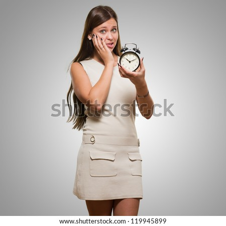 Worried Woman Holding Alarm Clock against a grey background - stock photo