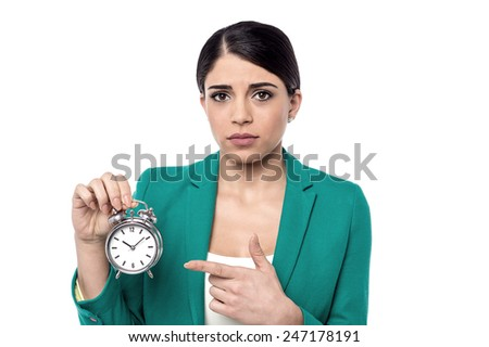 Worried woman holding and pointing alarm clock - stock photo