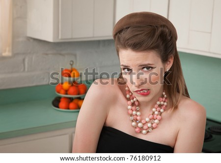 Worried woman in a kitchen bites her lip - stock photo