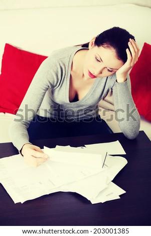 Worried woman is looking her bills. Finance concept. - stock photo