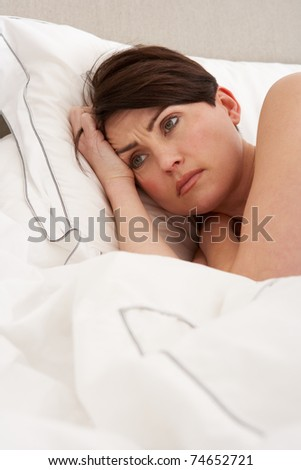 Worried Woman Laying Awake In Bed - stock photo