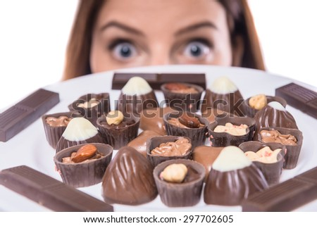 Worried woman on diet looking at plate with chocolates. Healthy lifestyle concept. - stock photo