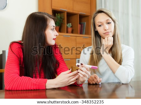 worried women with pregnancy test at table in home interior