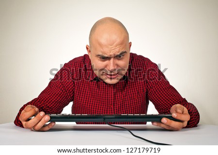 Worried young adult bald man sitting at the office table in front of the computer keyboard
