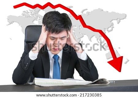 Worried young asian businessman sitting with head in hands at office desk