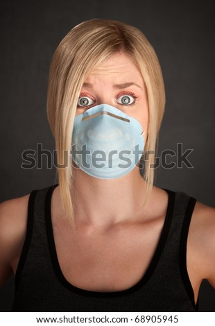 Worried young blonde woman with surgical mask on a grey background - stock photo