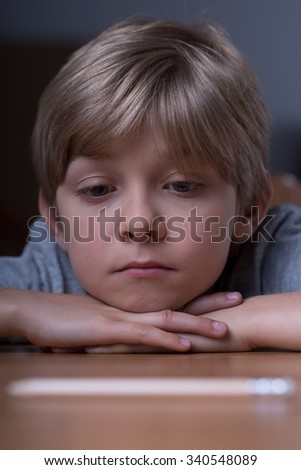 Worried young boy lying on the desk - stock photo