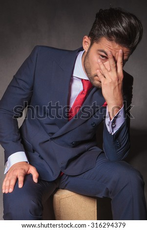 Worried young business man sitting while holding his hand on his face. - stock photo