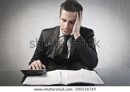 Worried young businessman calculating the closing balance - stock photo