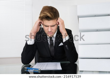 Worried young businessman reading document at desk in office - stock photo