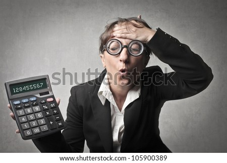 Worried young businesswoman holding a calculator - stock photo