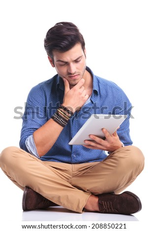 worried young casual man reading on a tablet pad computer, thinking  - stock photo