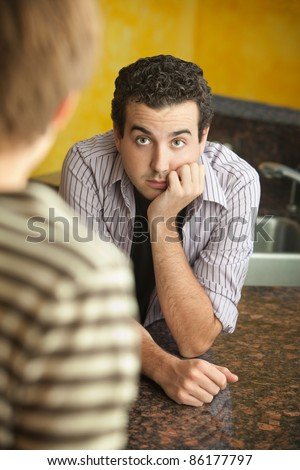 Worried young Caucaisian man with hand on chin in kitchen - stock photo