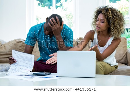 Worried young couple discussing on bills at home - stock photo