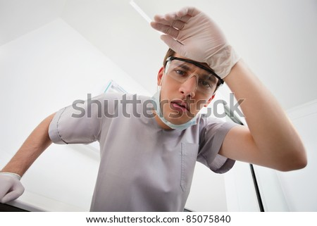 Worried young dentist at clinic - stock photo