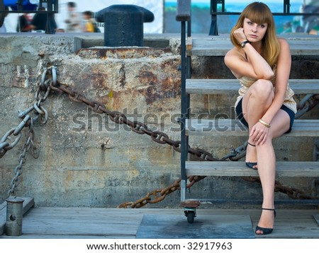 Worried young girl siting on wooden stairs - stock photo