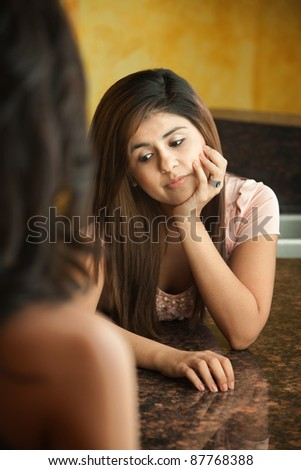 Worried young Hispanic teen with hand on chin - stock photo