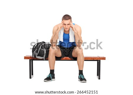 Worried young man in sportswear sitting on a wooden bench, looking down and wondering, isolated on white background - stock photo