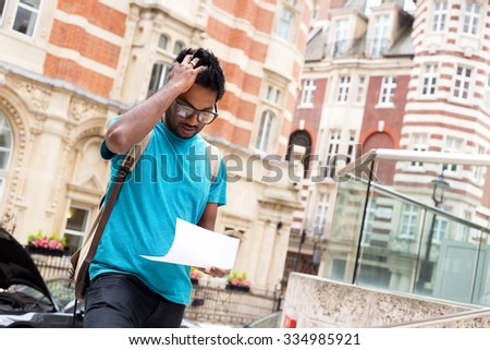 worried young man reading a letter in the street - stock photo