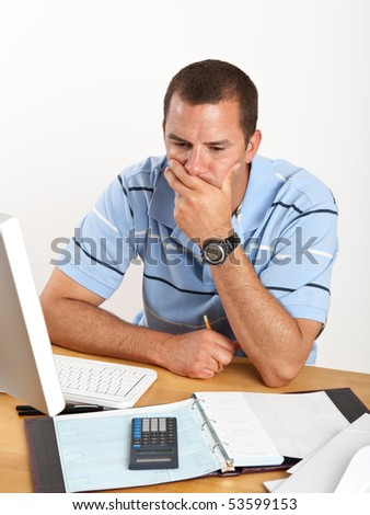 Worried young man, stressed out over bills and finances, sitting at desk with checkbook and computer. - stock photo