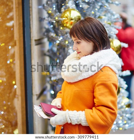 Worried young woman holding purse with Russian roubles in shopping mall decorated for Christmas, financial crisis in Russia concept - stock photo