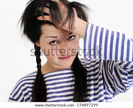 worried young woman touching her hair, looking at camera  - stock photo