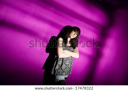 Worried young woman with arms crossed against pink wall with strong shadow. Sad girl in depression concept - stock photo