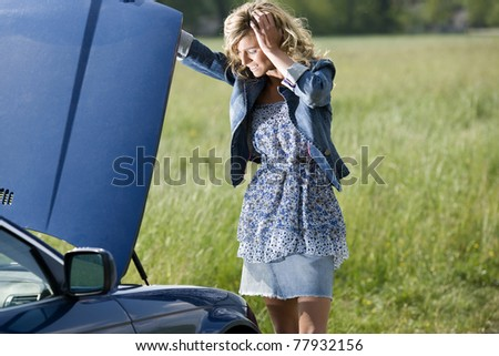 Worried young woman with her broken car - stock photo