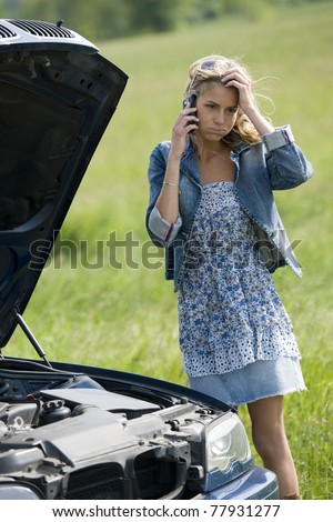 Worried young woman with her broken car, calling for assistance - stock photo