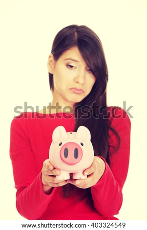 Worried young woman with piggybank. - stock photo