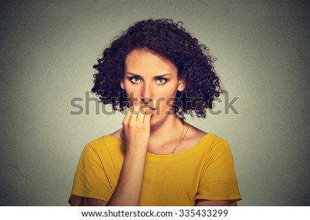 Worries. Closeup portrait nervous looking woman biting her fingernails craving something anxious isolated on gray wall background. Negative human emotion facial expression body language perception - stock photo