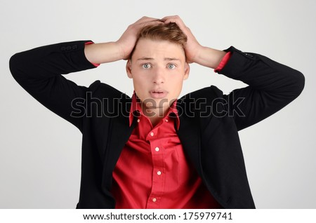 Worry, sadness, desperation. Young business man holding his head frowning with worry. Man with different facial expressions. - stock photo