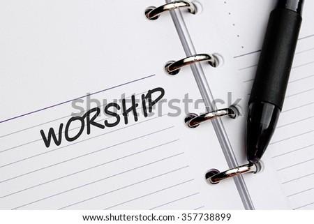 WORSHIP word written on notebook - stock photo