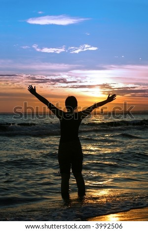 worshipper against incredible summer sunset on the beach - stock photo
