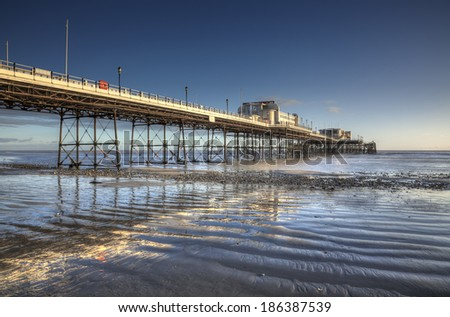 Worthing Pier reflected in wet sand at low tide, illuminated by late afternoon sunshine.  - stock photo